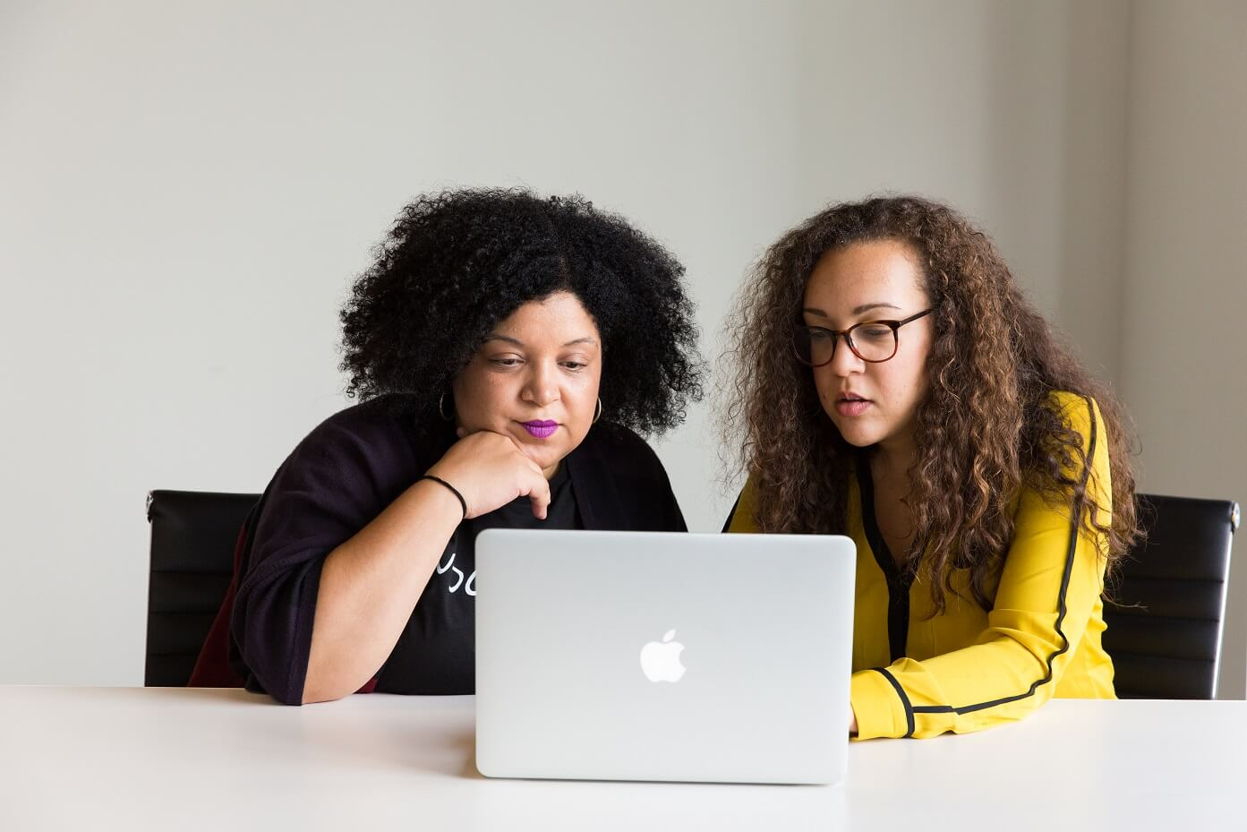 Two women using a laptop.